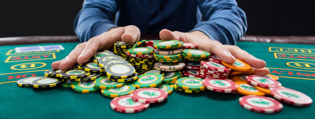 "Poker player sitting at a poker table trying to hide his expressions and going ""all in"" pushing his chips forward"